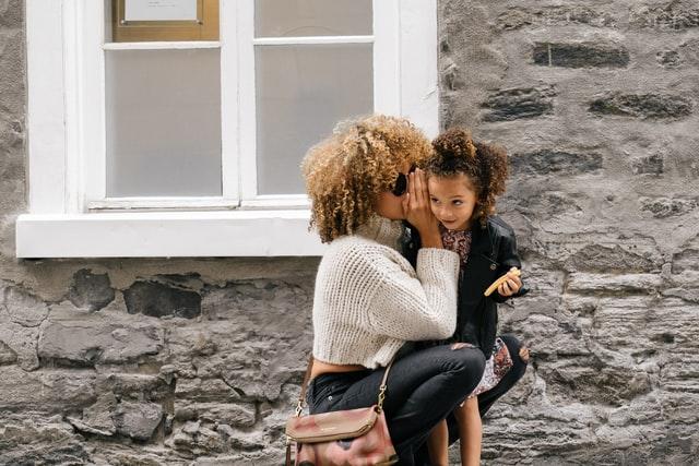 Mulher e menina negras, mulher agachada ao lado da menina cochichando em seu ouvido.