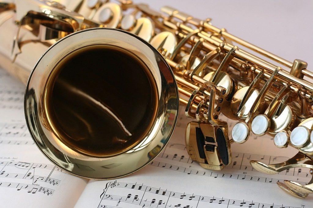 Imagem de um saxofone dourado sobre um caderno de música.