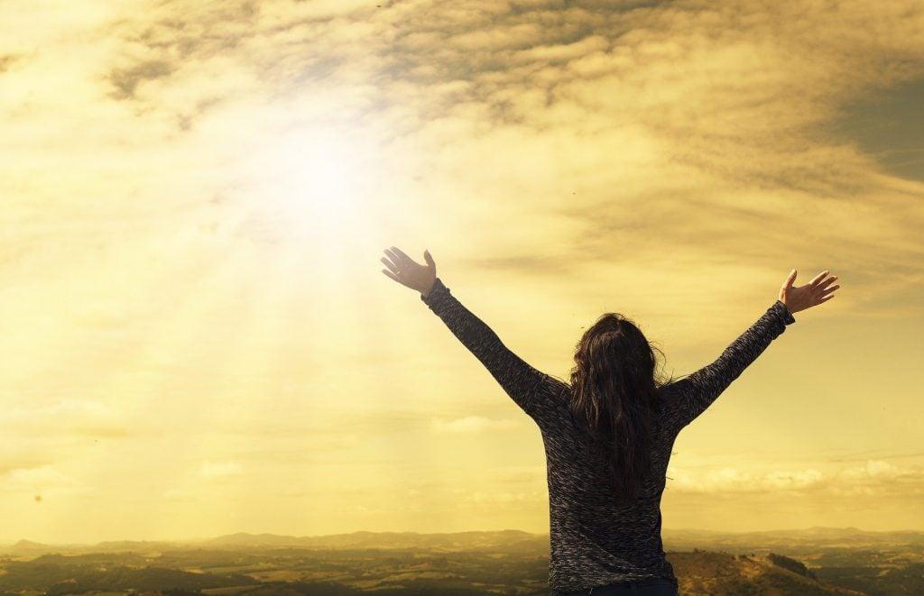 Imagem de uma mulher do alto de uma montanha. Ela está olhando para o sol de braços abertos, dando boas-vindas a ele.