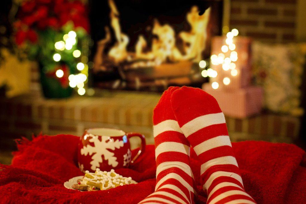 Imagem de um pé usando uma meia nas cores vermelho e branco. A pessoa está sentada no sofá com os pés elevados. Ela está sozinha passando o natal em isolamento. Ao lado um caneca vermelha e um pires com biscoitos natalinos.