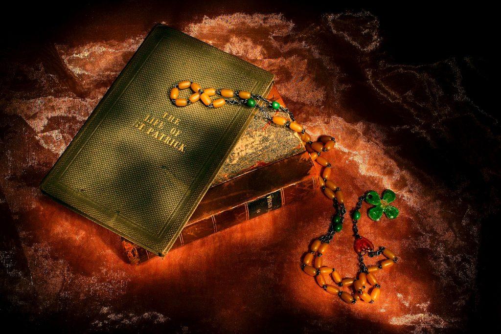 Imagem de uma bíblia e sobre ela um livro que traz a história de São Patrício. O livro tem capa dura na cor verde e ao lado um terço de contas e na ponta um trevo-de-quatro-folhas na cor verde.