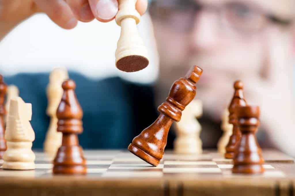 Imagem de um tabuleiro de xadrez e um homem movimentando uma das peças.