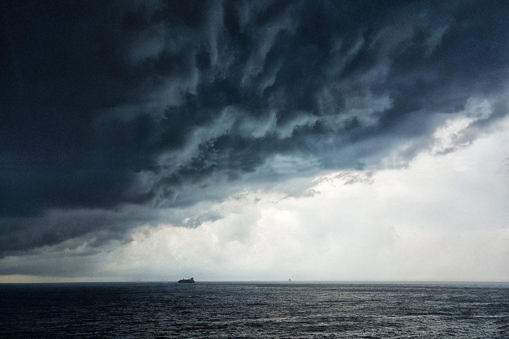 Imagem do oceano e sobre ele uma nuvem escura formando uma tempestade. Ao fundo um navio.