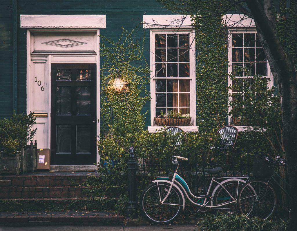 Imagem da frente de uma casa com muro coberto por uma folhagem. A porta da casa é pintada de preto e as janelas possuem um beiral na cor branco. Na frente da casa uma bicicleta de modelo vintage. Free-Photos por Pixabay