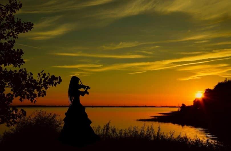 Imagem de uma violinista tocando uma música em frente a um lindo por do sol.