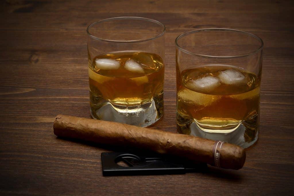Imagem de dois copos com whisky e gelo e um charuto apagado. Eles estão dispostos sobre uma mesa de madeira.