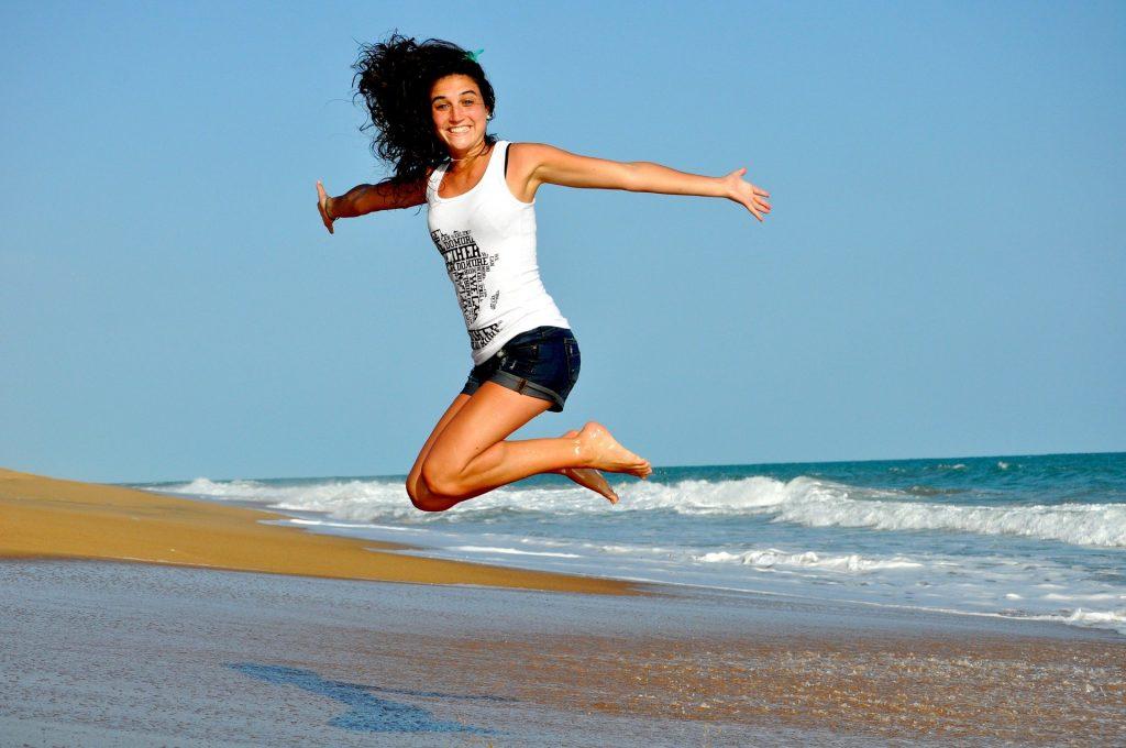 Imagem de uma mulher de cabelos escuros. Ela usa um short jeans e uma camiseta regata branca. Ela está dando um salta de braços abertos na areia da praia.