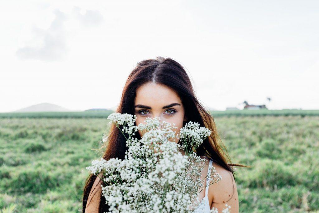 Imagem de uma bela mulher de cabelos longos e escuros em um campo. Ela segura em suas mãos um buquê de flores brancas.