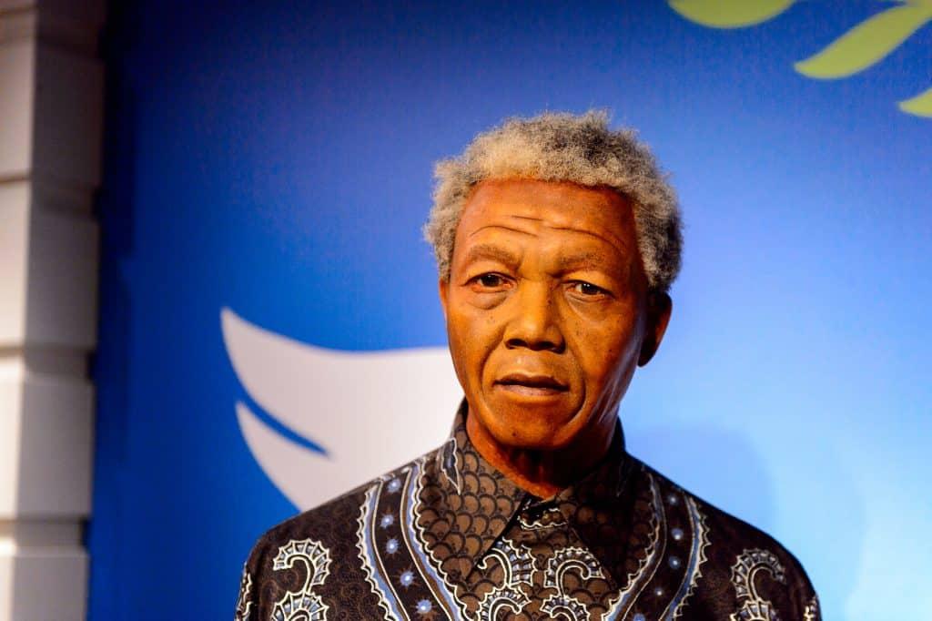 Imagem com fundo azul e a frente a foto de Nelson Mandela. Ele está usando uma camisa marrom com detalhes em branco e azul.