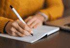 Pessoa escrevendo algo em páginas de um caderno