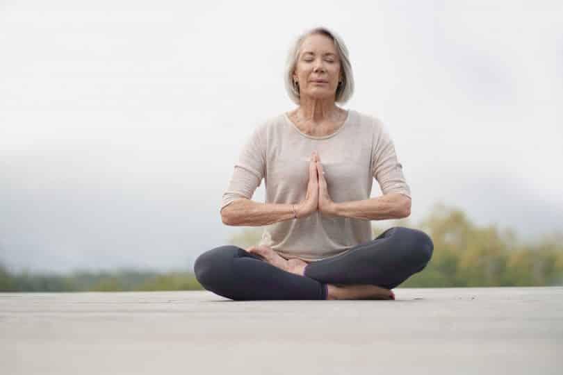 Mulher idosa em momento meditativo.