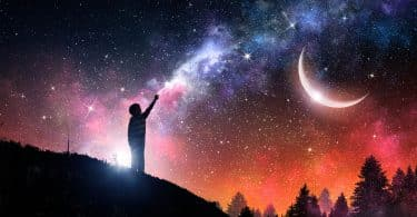 Silhueta de um menino em pé. Ao fundo há uma galáxia e uma meia-lua.