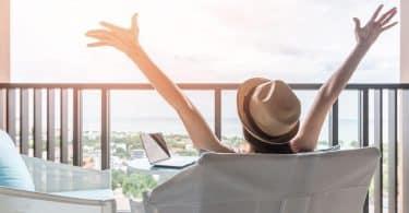 Mulher com as mãos para o alto admirando a paisagem.