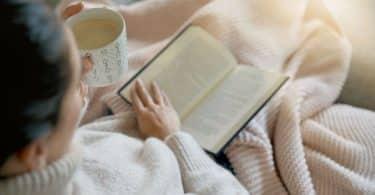 Mulher lendo livro na cama