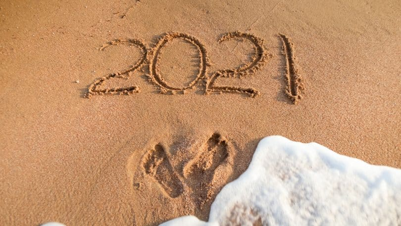 Número 2021 escrito na areia. Marcas de pés estão abaixo, seguidos por água de mar.