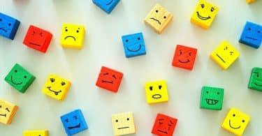 Pequenos blocos de madeira coloridos com rostos desenhados.