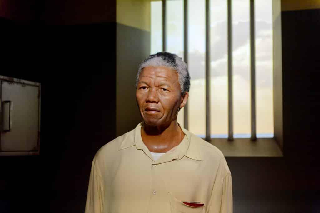 Imagem de Nelson Mandela na cela da prisão. Ele usa uma camisa bege e por baixo dela  uma camiseta de malha na cor branca.
