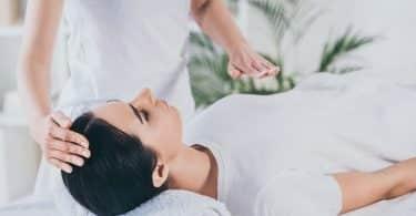 Mulher branca deitada numa maca com mão brancas sobre o corpo dela.