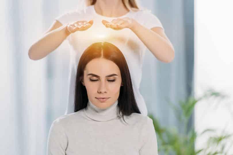 Mulher branca com mãos sobre cabeça de mulher branca sentada.