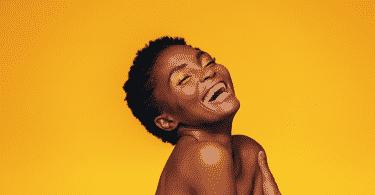 Modelo rindo com maquiagem em fundo amarelo