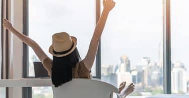 Mulher sentada em uma cadeira giratória observa cidade do alto de um prédio. Seus braços estão erguidos e ela usa um chapéu.