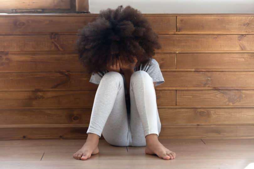 Menina negra sentada com as mãos no rosto e joelhos levantados.