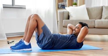 Homem branco fazendo abdominais no chão.