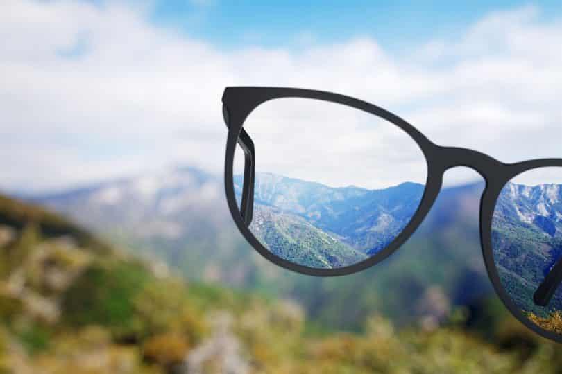 Visão da natureza pelo óculos com o fundo desfocado.