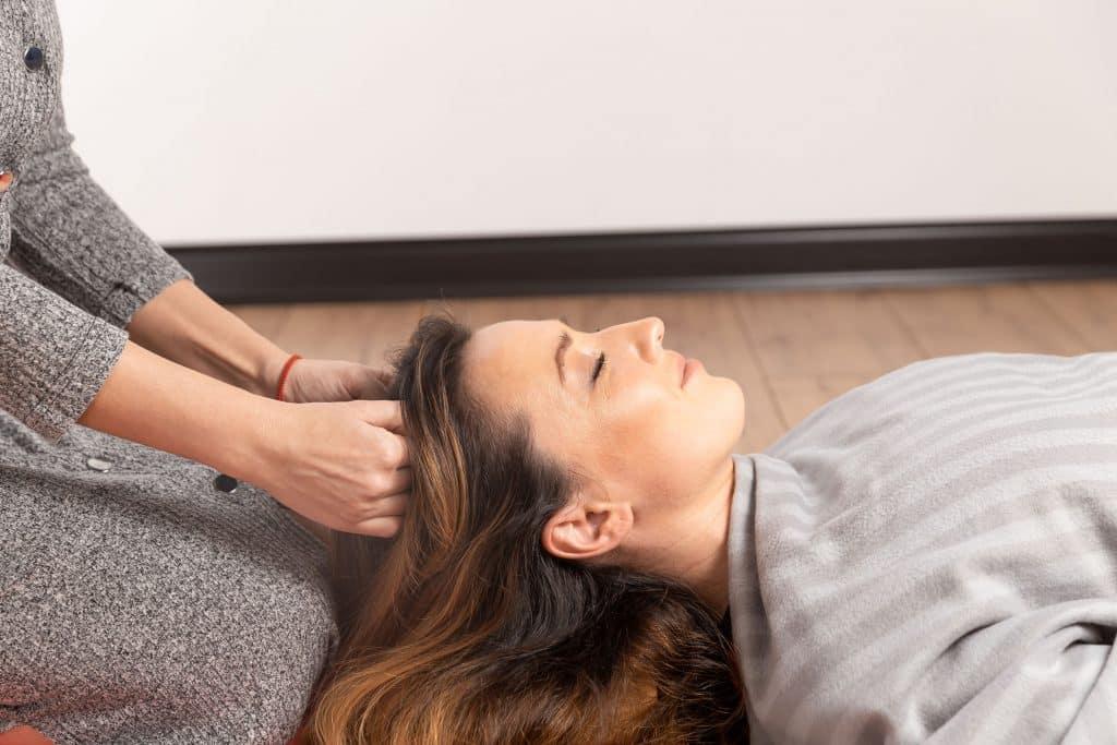 Mulher branca deitada de olhos fechados recebendo massagem na cabeça.