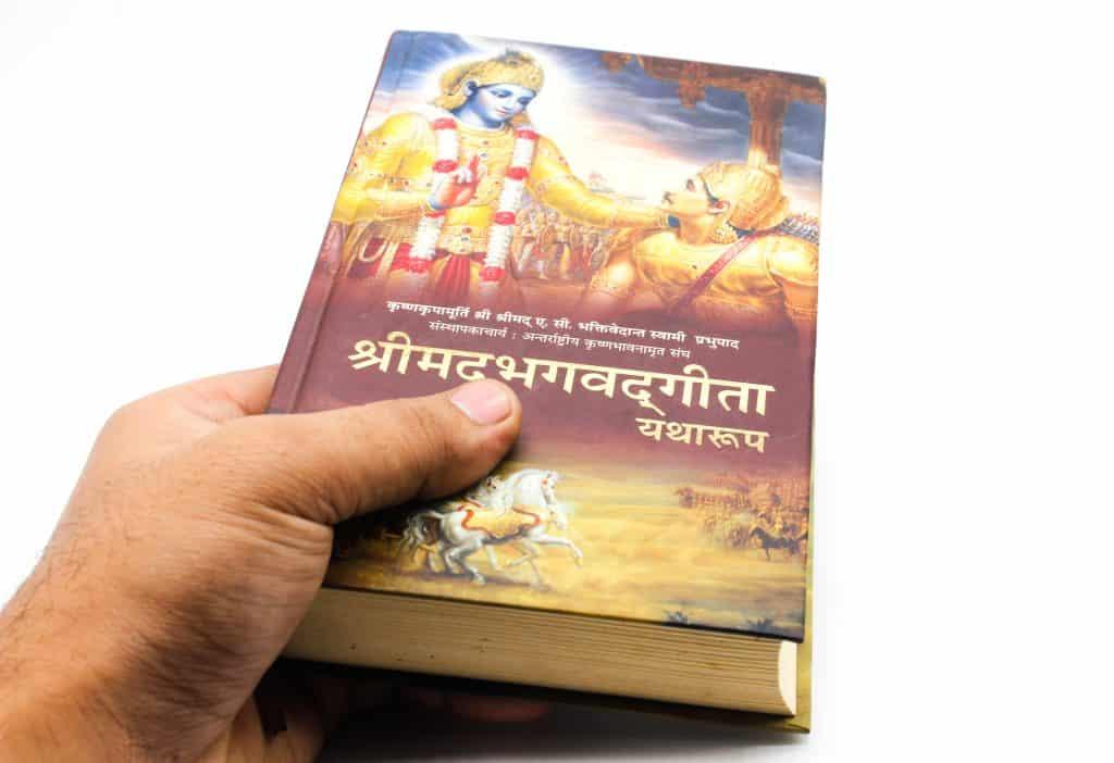 Imagem de fundo branco e em destaque o livro fechado denominado Bhagavad Gita, uma obra importante da religião hindu.