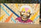 Imagem de um muro pintado com a imagem do rosto de Nelson Mandela. Trata-se de uma homenagem ao ativista.
