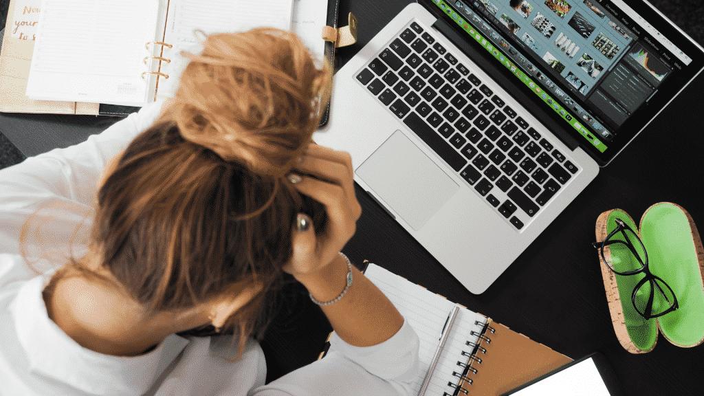Mulher estressada no escritório com as mão na cabeça