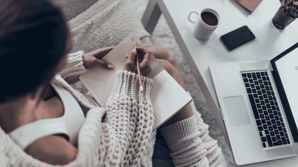 Mulher sentada no chão do quarto pensando o que escrever em seu caderno