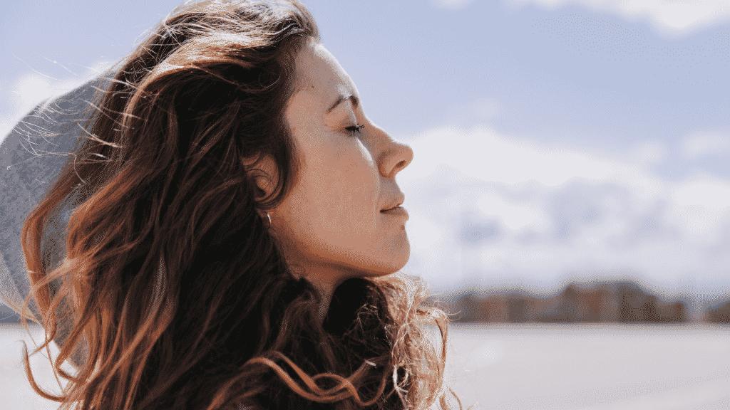 Mulher de olhos fechados sentindo a brisa do vento