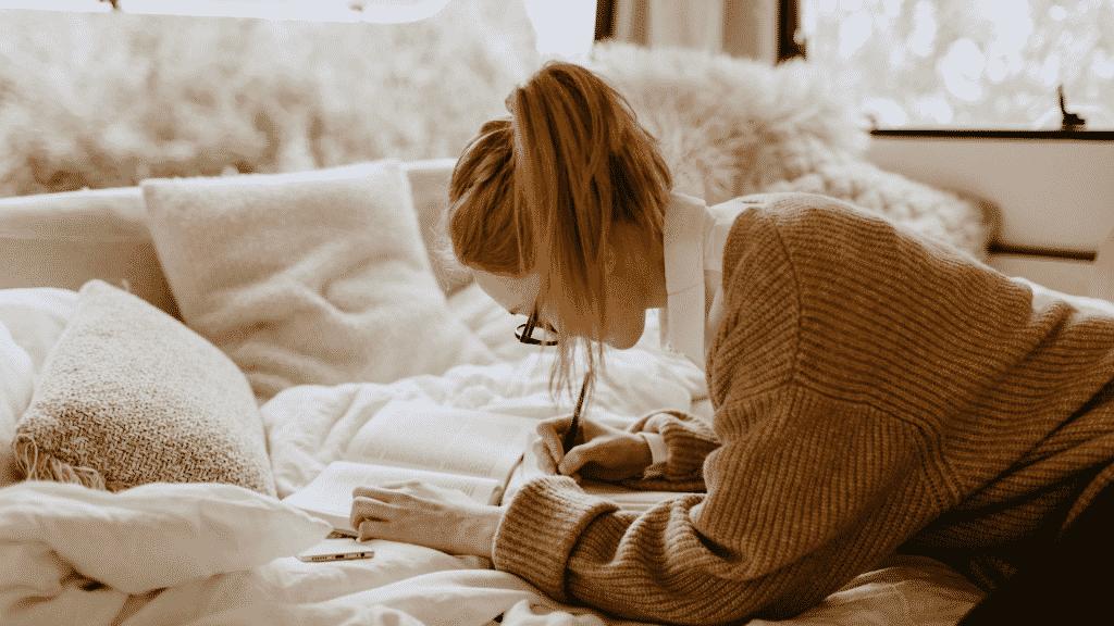 Garota de óculos deitada na cama escrevendo em seu caderno
