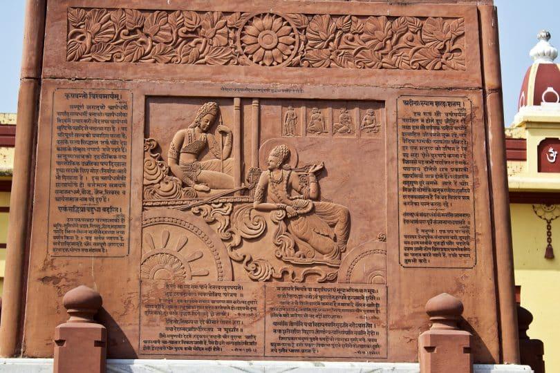 Imagem de um monumento na Índia onde traz uma parte de um trecho do livro Bhagavad Gita.