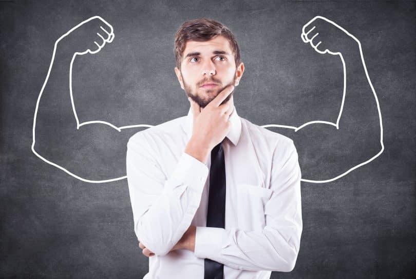 Representação simbólica de força: um homem com semblante pensativo. Sob ele, há um quadro negro com a imagem de dois bíceps desenhada.