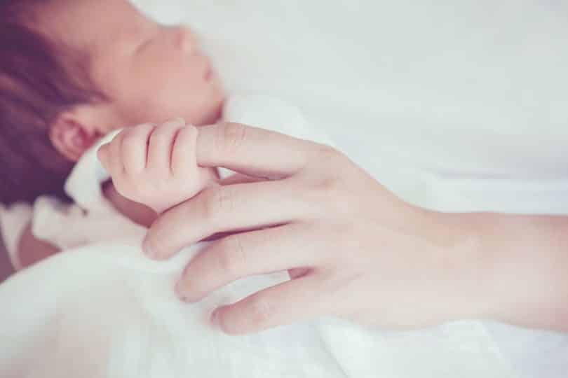 Bebê segurando dedo da mãe