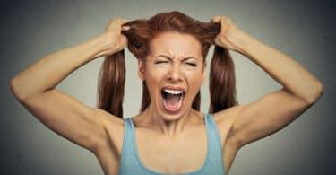 Mulher com a expressão facial estressada e mãos segurando os cabelos.