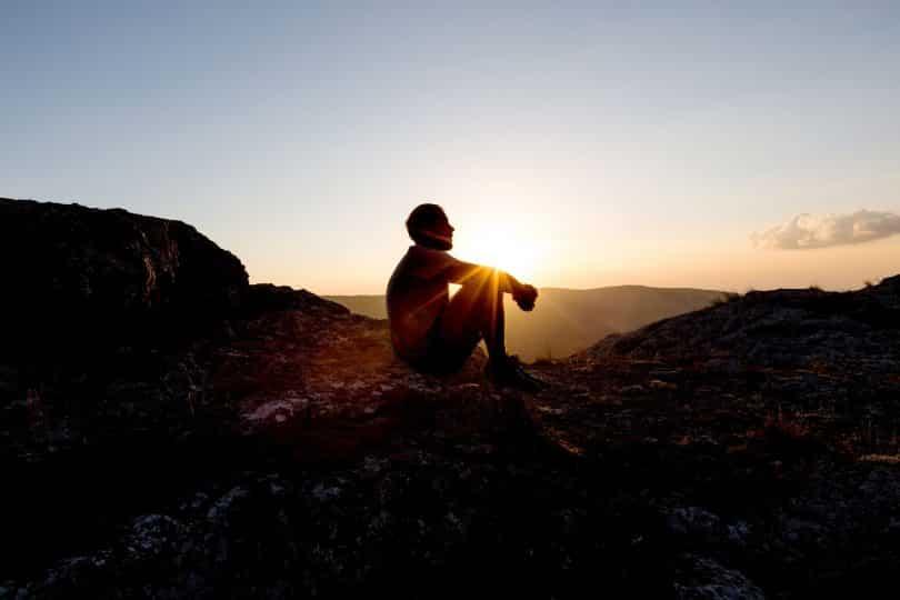 Silhueta de homem sentado numa montanha.