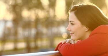 Mulher apoiada sobre base de madeira olha para o horizonte.