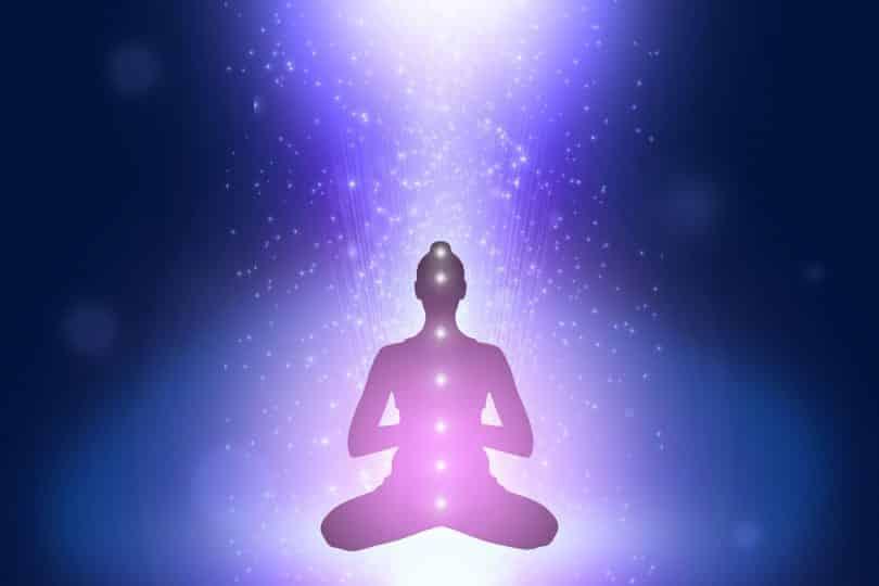 Silhueta de uma mulher em posição de meditação com luzes roxas ao seu redor.
