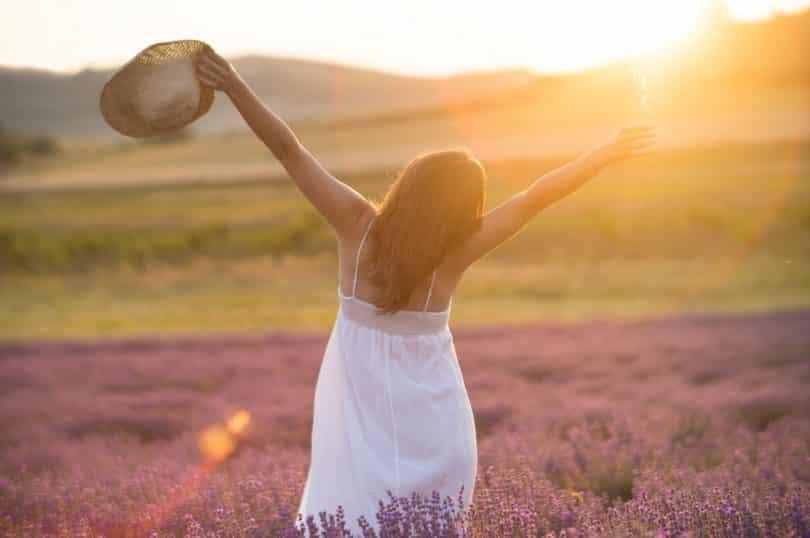 Mulher jovem com um vestido branco e um chapéu de palha em pé no meio de um campo com o pôr do sol ao fundo.