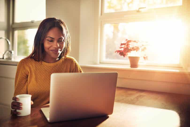 Mulher segura uma caneca de café e mexe em computador.