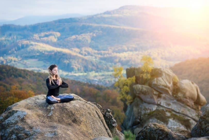 Mulher branca meditando sentada numa rocha.