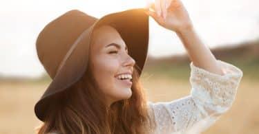Mulher branca com expressão sorridente segurando um chapéu na cabeça.