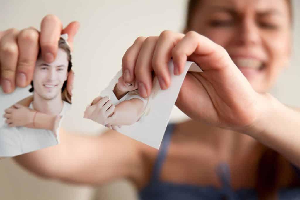 Mulher branca rasgando foto de casal.