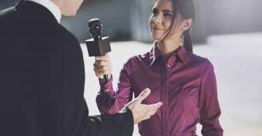 Um jornalista com uma camisa bordô sorrindo ouve um homem.