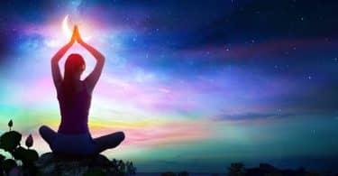 Silhueta de uma mulher sentada em posição de meditação com os braços estendidos. Ao fundo há uma paisagem noturna.