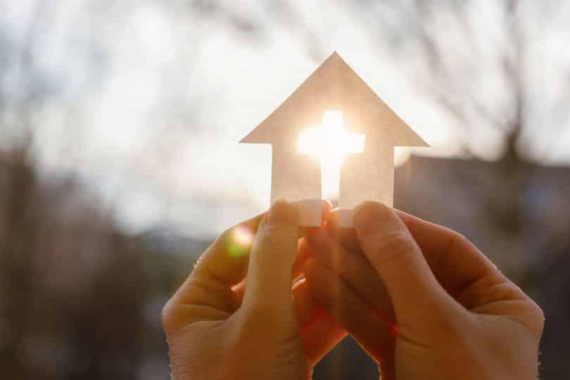 Mão com uma casa de papel e uma cruz sobre um fundo de nascer do sol.